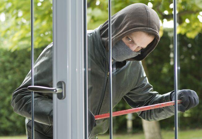 81071852 - Burglar breaking in a house - © sdecoret